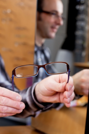 salesperson offering new glasses in a shop photo