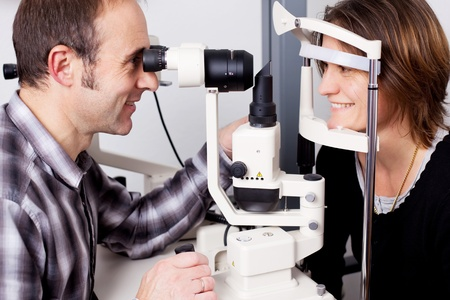 eye disease: confident optician examine female patients eyes with measurement machine