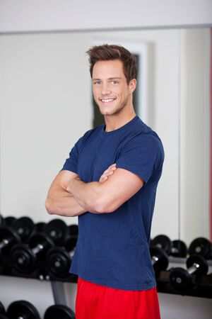 Portrait of confident young man with arms crossed standing in gym photo