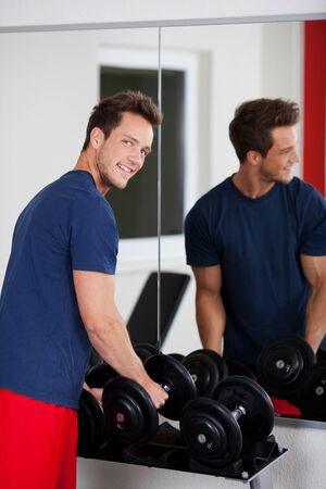 Man holding dumbbells to exercise cross fit fitness workout photo