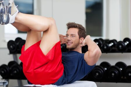 toning: Young man exercising in gym Stock Photo