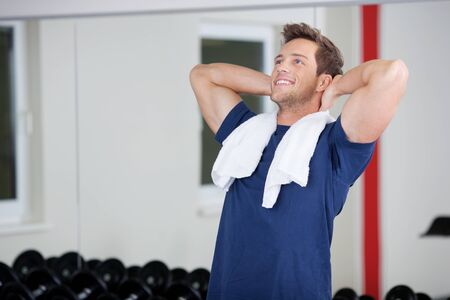 Happy young man doing stretching exercise in gym photo