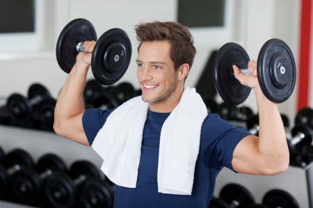 sports hall: Happy young man lifting dumbbells in gym