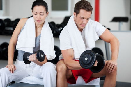 Sitting man and woman lifting dumbbell in gym photo