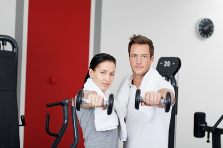 Healthy couple holding dumbbells in the gym with towel around their neck photo