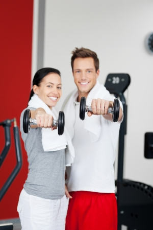 Portrait of happy young couple lifting dumbbells in gym photo