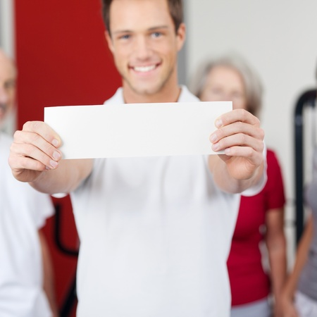 blank center: Portrait of young man displaying blank paper with group in background at gym Stock Photo