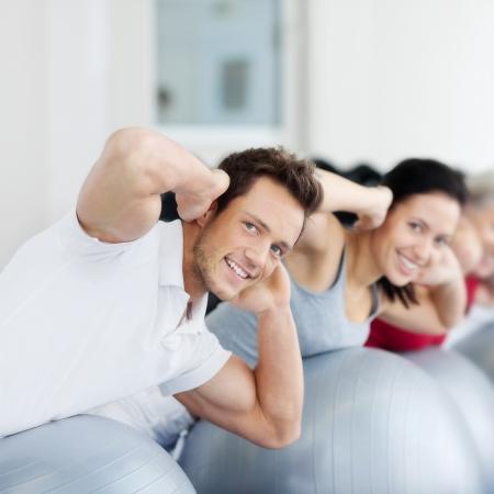 motion: Porträtt av glad grupp utövar på schweizisk boll