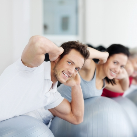 back exercise: Portrait of happy group exercising on Swiss ball