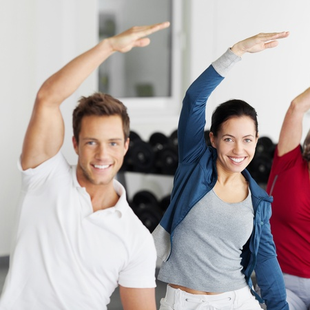 Portrait of happy smiling group with arms raised doing stretching exercise in gym photo