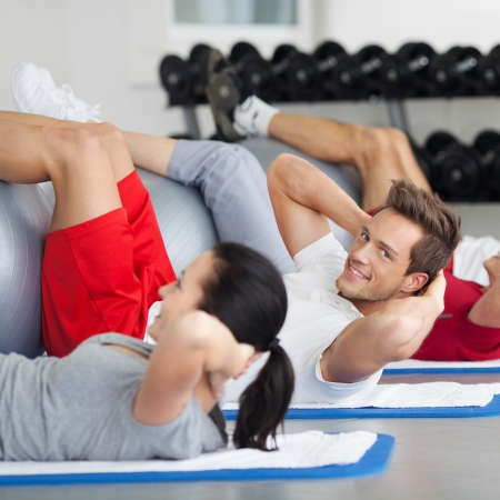 body toning: Side view of group with fitness ball practicing crunches in gym Stock Photo