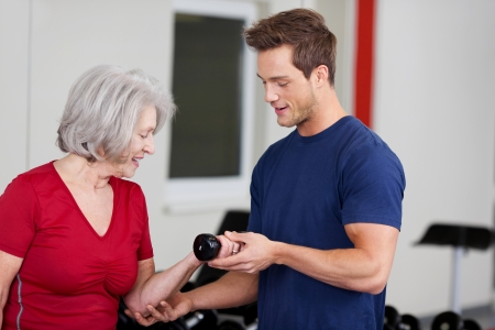 Handsome young male fitness trainer instructing an elderly woman on the correct way to fit weights with a dumbbell in a gym photo