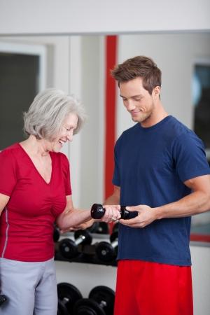 aide � la personne: Jeune entra�neur beau m�le debout avec une femme �g�e dans le gymnase lui montrant comment Flex et lever le bras tout en maintenant un poids d'halt�re