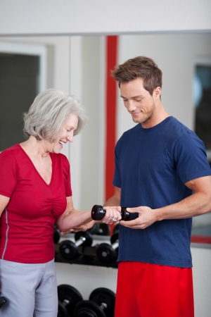 personal trainer woman: Young handsome male trainer standing with a senior woman in the gym showing her how to flex and raise her arm while holding a dumbbell weight