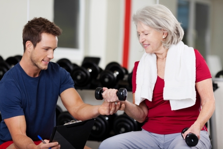 Handsome male instructor assisting senior woman in lifting dumbbells at gym