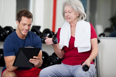 writing activity: Handsome young male trainer instructing an active senior woman in the gym writing her progress on a clipboard as she lifts weights with a pair of dumbbells Stock Photo