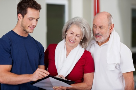 Male instructor showing health results on clipboard to senior couple at gym