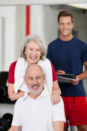 Active senior couple posing together in the gym with a handsome young male fitness trainer in the background photo