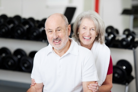 Smiling affectionate senior couple at the gym posing in front of racks of equipment with friendly smiles photo