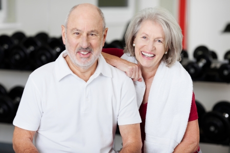 Head and shoulders portrait of a smiling friendly senior couple in a gym posing in front of racks of equipment, conceptual of an active healthy lifestyle photo