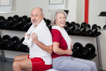 Senior couple exercising at a gym sitting back to back with towels around their necks in front of racks of weights
