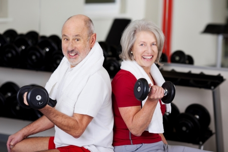 older women: Portrait of happy senior couple lifting dumbbells while sitting together in gym