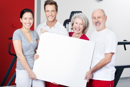 Group of young and elderly fitness enthusiasts standing in a gym laughing and smiling with a blank white sign in their hands