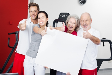 mother in law: Portrait of happy family with blank billboard standing together while gesturing thumbs up in gym