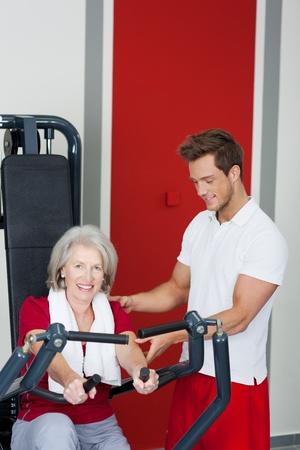 aide à la personne: Portrait de femme âgée étant aidé par le formateur masculin dans l'utilisation de la machine à ramer au gymnase