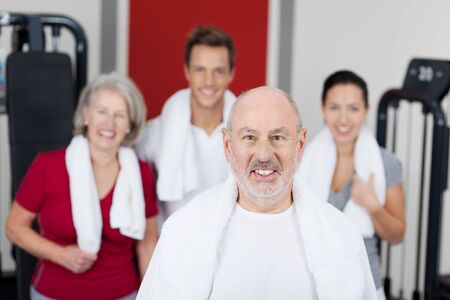 Portrait of senior man smiling with family in gym photo