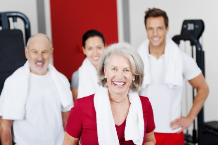 Portrait of senior woman laughing with family smiling in background at gym photo