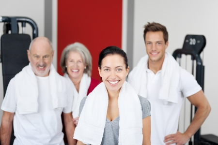 Smiling motivated group of young and old people at the gym with focus to an attractive young woman in the foreground Stock Photo