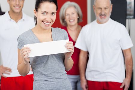 daughter in law: Portrait of happy young woman holding blank paper with family in background at gym
