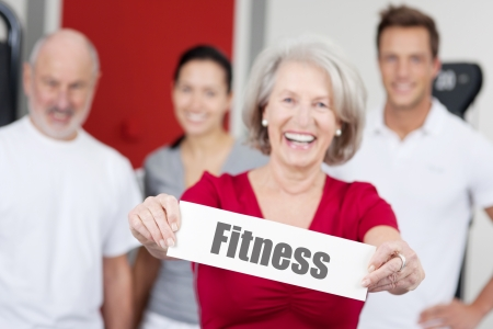 Portrait of happy senior woman holding Fitness sign with family in background at gym photo