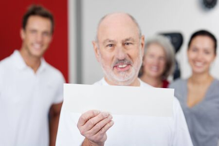 son in law: Portrait of senior man displaying blank paper with family in background at gym