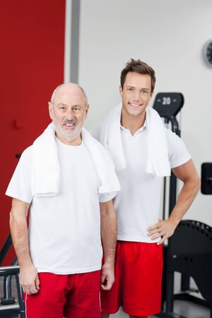 Portrait of happy father and son in sports clothing standing at gym photo