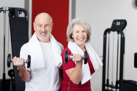 levantar pesas: Feliz pareja senior activa llena de vitalidad de un estilo de vida sano de trabajo con pesas en un gimnasio