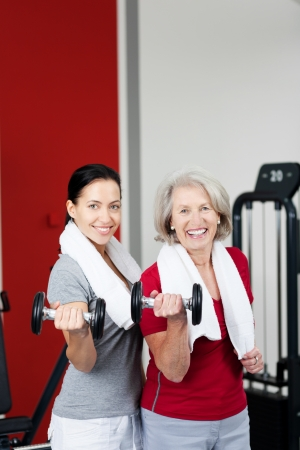 Woman power - an attractive motivated elderly mother and her daughter stand together training in a gym using dumbbells to strengthen and tone their arm muscles, with copyspace photo
