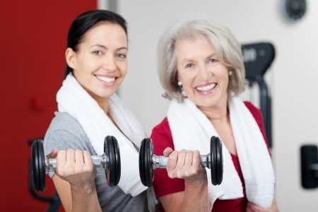Portrait of happy mother and daughter lifting dumbbells in gym Stock Photo