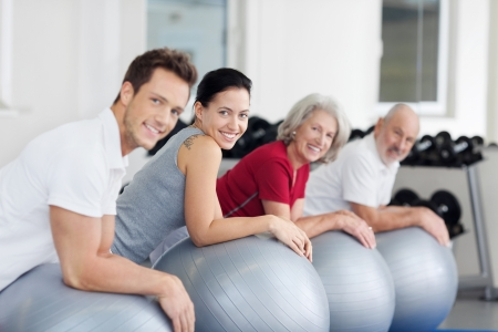 Group of diverse young and elderly people exercising in a gym using pilates balls with focus to a beautiful happy young woman smiling at the camera photo
