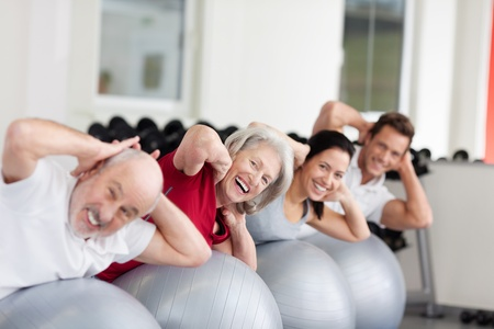Smiling attractive elderly woman training in a diverse group of people using pilates balls in a gym, receding oblique row photo