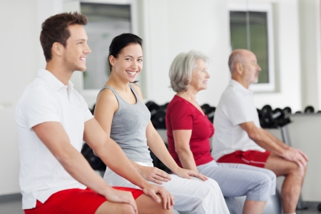 Group of people training in a gym with focus to a smiling young woman sitting practising her posture seated on a pilates ball photo