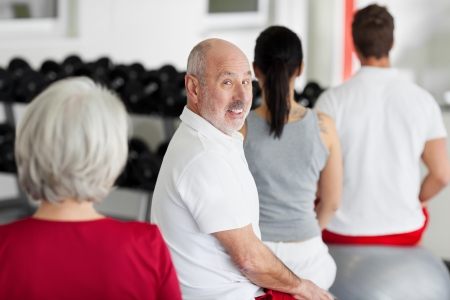 father in law: Portrait of senior man with family sitting on Swiss balls in gym