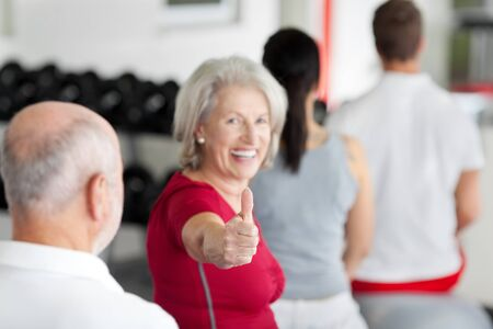 Portrait of happy senior woman gesturing thumbs up sign with family sitting in gym photo
