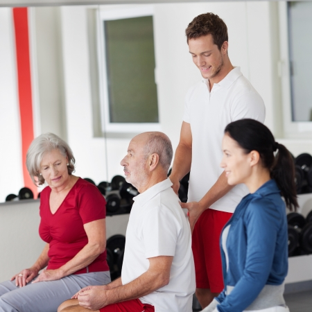 Handsome young male trainer correcting the posture of an elderly man sitting on a pilates ball at the gym photo