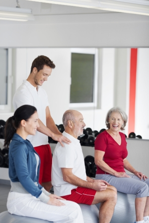 fit ball: Trainer helping a senior man at the gym correcting his posture as he sits balancing on a pilates ball watched by his laughing wife Stock Photo