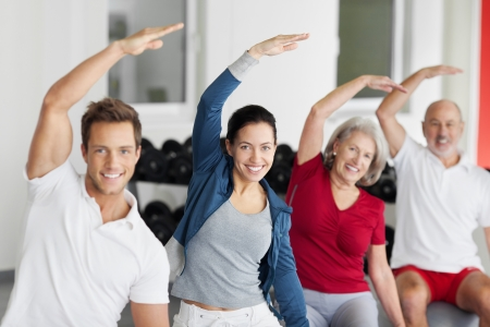 indoors: Portrait of happy family with arms raised doing stretching exercise in gym Stock Photo