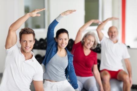 hombres haciendo ejercicio: Entusiasta grupo de personas jóvenes y mayores que hacen ejercicios aeróbicos en un gimnasio, con especial atención a un joven sonriente hermoso en el frente