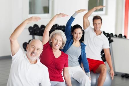 aerobica: Gruppo di diversi giovani e meno persone che fanno esercizi di aerobica in palestra seduto su palle pilates alzando le braccia in aria Archivio Fotografico