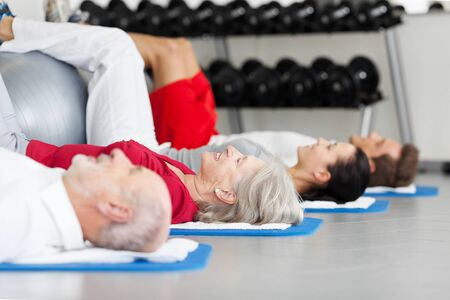 son in law: Side view of family exercising while lying on mat at gym Stock Photo